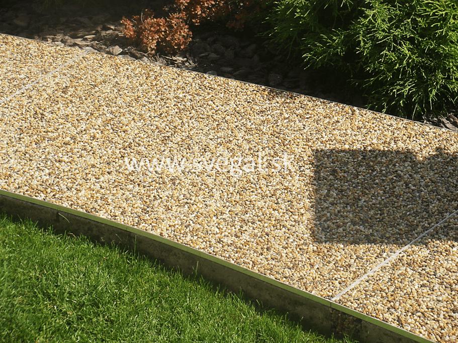 Kamenný koberec na chodníku v záhrade. Okrajové lišty zabraňujú vylamovaniu kamienkov, stredové lišty fungujú ako pracovná dilatácia.