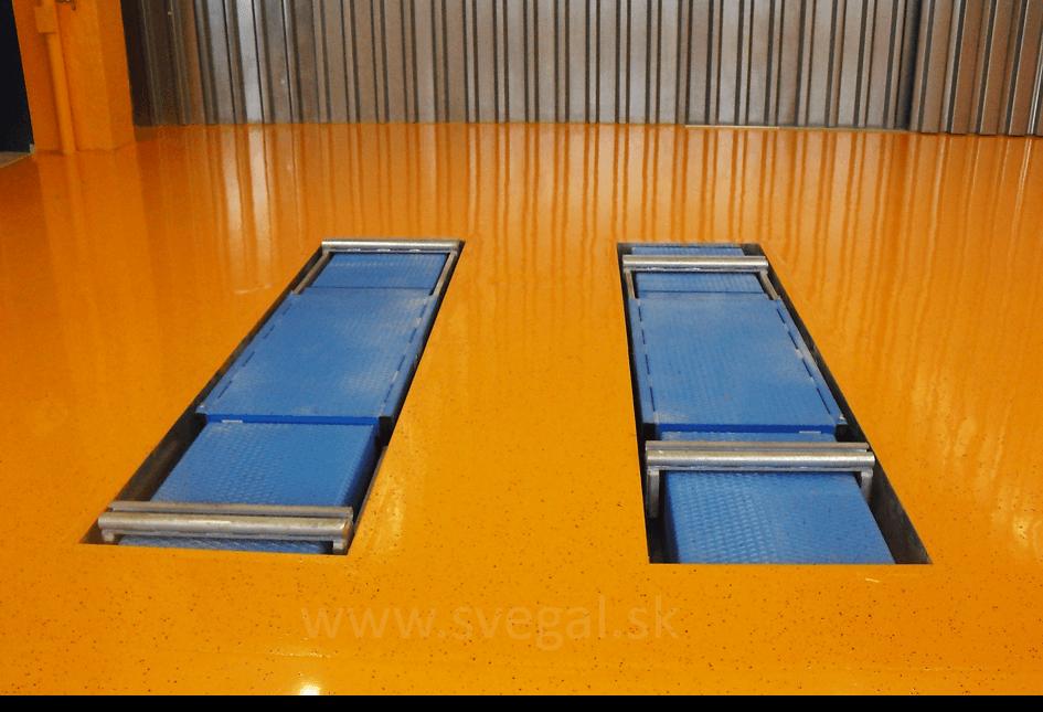 Betónová podlaha na stanici STK upravená epoxidovou stierkou s presypom akrylových čipsov HERBOL.