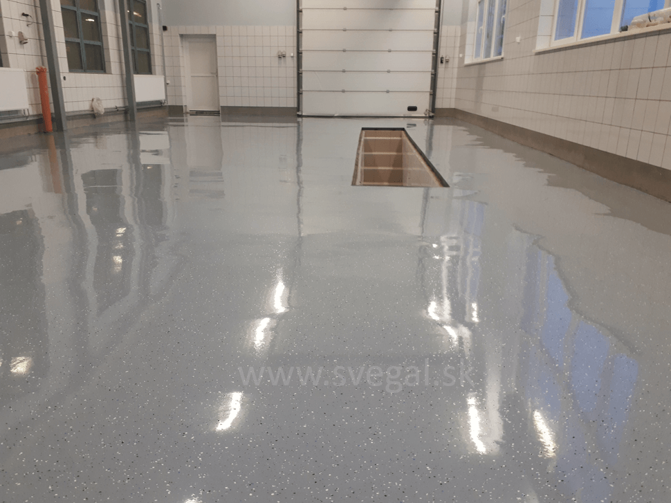 Liata podlaha v garáži upravená zmesou čiiernych a bielych akrylátových čipsov. Účel čipsovania je opticky zvýrazniť povrch a zvýšiť protišmykovosť.